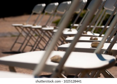 Rocks lining chairs at an outdoor wedding.