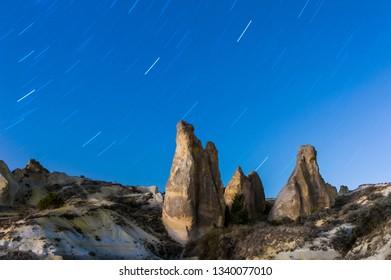 Rocks looking like mushrooms under star trails in Cappadocia at night, Turkey