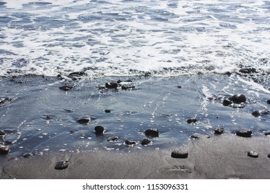 Rocks lying in black sand on the rocky, sandy shoreline of Pololu Valley in North Kohala, Hawaii, USA