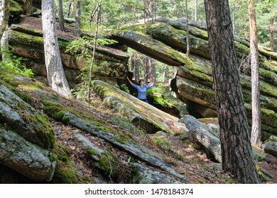 Rocks made up of horizontal layers. Trees grow on stones. A wide crack created a passage in the rock. A woman is standing under a pile of flat stones.