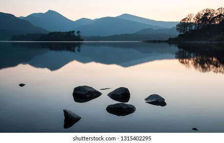 Rocks and the mountains of the Derwent Fells are reflected in the calm waters of Derwent Water lake in England's Lake District National Park.
