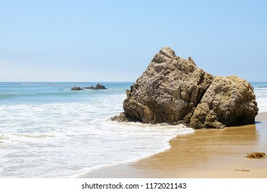 Rocks in the ocean on a sunny day at Broad Beach in Malibu, California.