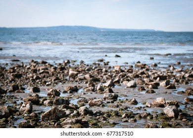 rocks on a beach with blue water and blue sky perspective shot