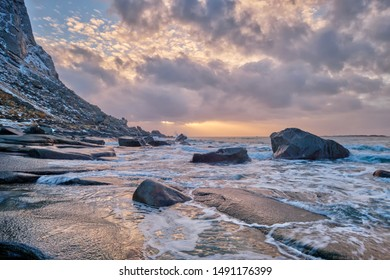 Rocks on beach of fjord of Norwegian sea in winteron sunset. Utakliev beach, Lofoten islands, Norway