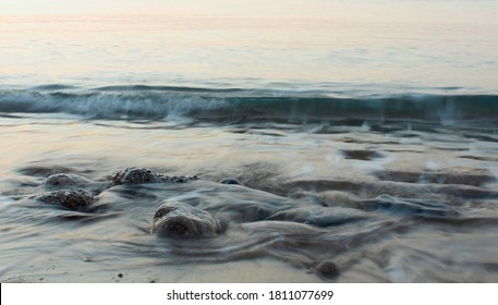 rocks on the beach are washed by the incoming wave of surf at dawn. The long exposure photo with smoothing the surface of the water.