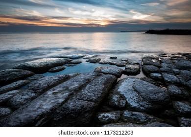 Rocks on the shoreline of Lake Ontario during sunset near Cobourg, Ontario