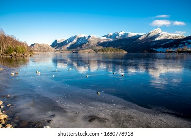 Rocks on top of ice crust of the frozen Oltedalsvatnet lake and scenic landscape of mountains, Gjesdal commune, Norway, February 2018
