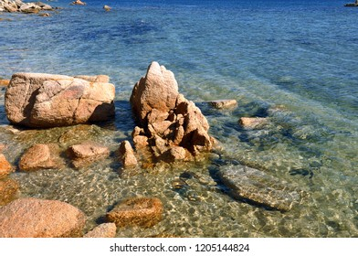 Rocks over and under the water split by waterline in a sea with clear water near Vladivostok city, Primorsky Krai, Far East, Russia.
