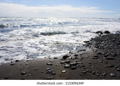 Rocks and pebbles lying in black sand on the rocky, sandy shoreline of Pololu Valley in North Kohala, Hawaii, USA