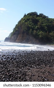Rocks and pebbles strewn along a black sand beach ending in a cliffside and meeting the Pacific Ocean in the Pololu Valley in North Kohala, Hawaii, USA