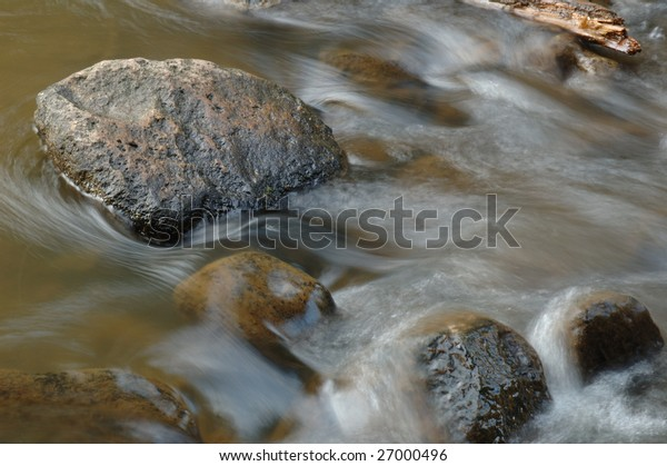 Rocks in the river washing by river in blurred motion