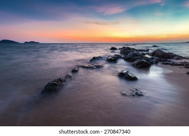 Rocks rock along the beach sand in the twilight.
