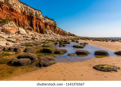 Rocks and rock pools at the base of the white, red and orange stratified cliffs at Old Hunstanton, Norfolk, UK