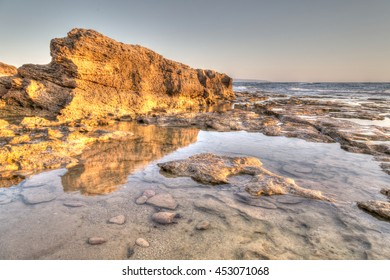 Rocks of sandstone reflecting the sunset light, Nahariya Beach, HDR painterly