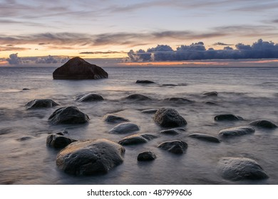 Rocks in the sea at sunset - long exposure photography