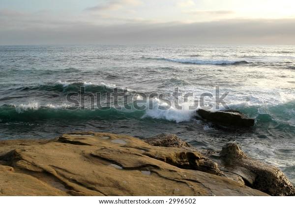 Rocks at Shore San Diego California Beach wit sun setting down