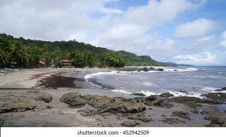 Rocks and a small bay with houses at Montezuma beach in Costa Rica