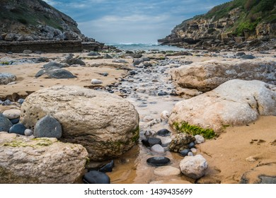 Rocks and small stream of water to go against the sea, in Praia da Samarra, flanked by mountains, Sintra Natural Park - Lisbon, Portugal