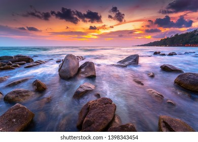 Rocks and smooth seascape in sunset at Mae Rumphueng Beach, Rayong in Thailand.