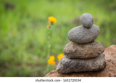 rocks stacked with a blurred background of wildflowers in a field