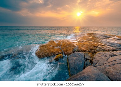 Rocks and stones at the ocean coast under a beautiful sunset sky with clouds on Sri Lanka island.