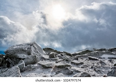 Rocks at the summit during a winter cold day. Sun pierces through the clouds.