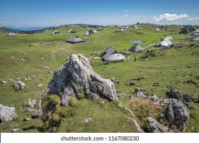Rocks and traditional wooden cottages in village on Velika planina (Big Pasture Plateau) with pastures, Slovenia