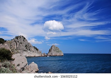 rocks trees clouds above blue sea