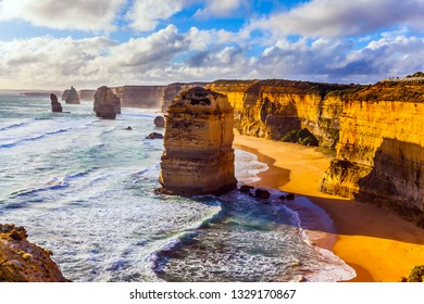 Rocks of the Twelve Apostles on grandiose coast of Australia. Powerful ocean surf at sunset. The concept of exotic, active and photo-tourism