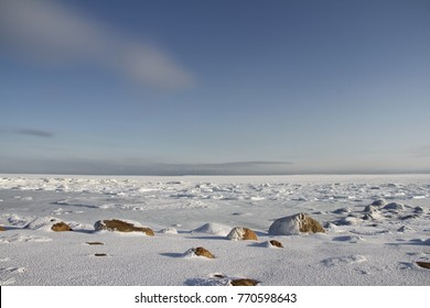 Rocks under snow and ice with a blue sky in the arctic, north of Arviat, Nunavut, Canada