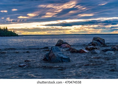Rocks in the water by the sea, while sun is setting through the clouds