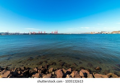 Rocks and water ripples against ships cranes against blue sky at high tide in Durban harbor in South Africa