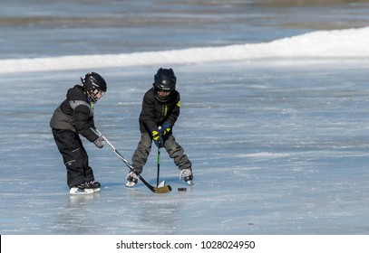 Rockwood Park, Saint John, New Brunswick, Canada - February 17, 2018: Winterfest, a free family event at Rockwood Park in Saint John. Two unidentifiable children play hockey on a frozen lake.