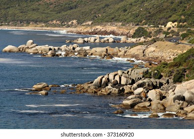 Rocky beach with coastal mountains, blue sky and sand in Cape town, South Africa.