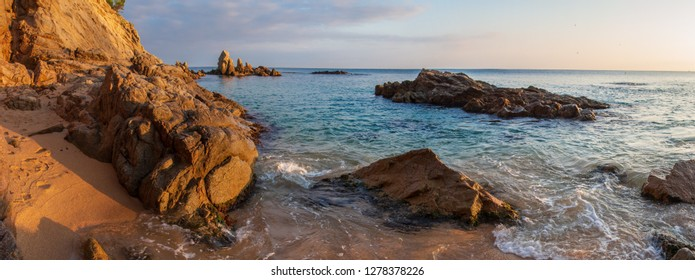 Rocky beach in Mallorca at sunrise. Spain seascape. Rocks on sandy beach in spanish resort. Sea morning landscape. Mediterranean coast