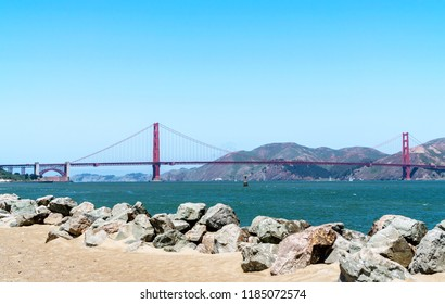 Rocky beach path with view of Golden gate bridge in background.