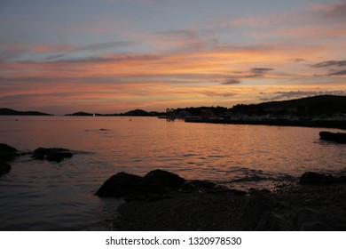 Rocky beach, sea shore during sunset. Summer, warm, holiday, evening. Twilight on the Adriatic Sea in Croatia. Vodice, Croatia. Colorful, orange sky. Beautiful dusk. Pleasant end of the day.