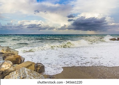 Rocky beach with sea view, waves of water and dark clouds on sky after storm