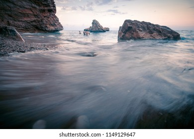 Rocky beach seascape at sunset time.  Swimmers in water as small details