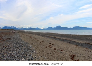 Rocky beach with snow capped mountains in the background