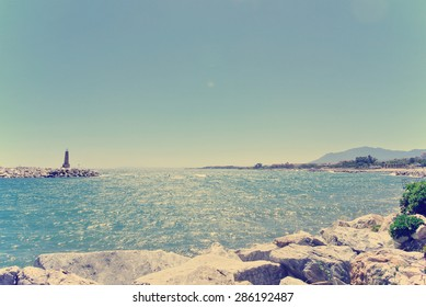 Rocky beach in Spanish luxurious seaside resort Puerto Banus, close to Marbella, on a sunny summer day. Filtered image in faded, washed-out, retro style; summer travel vintage concept.