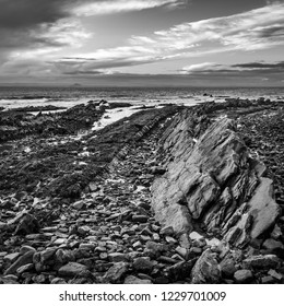 The rocky beach at St Monans in Fife, Scotland where volcanic rock formations protrude through the surface