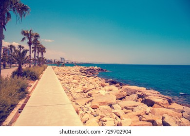 Rocky beach in the summer morning. Concrete embankment in Limassol, Cyprus
