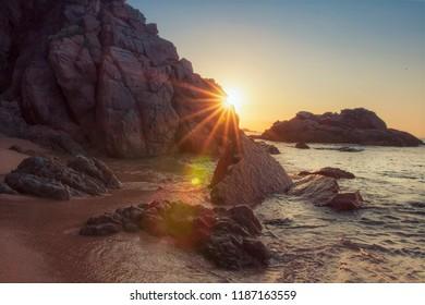 Rocky beach at sunrise with sunrays. Vivid sunbeams behind rock on sea beach. Tropical nature in morning. Paradise lagoon in spain. Rocks and stones on sandy beach Cala sa Boadella in Lloret de Mar