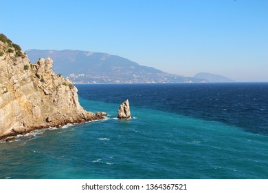 The rocky Black Sea coast of the Crimean peninsula near the town of Gaspra, part of Big Yalta. Above the blue water of a picturesque bay rises a cliff with a small statue of an eagle.