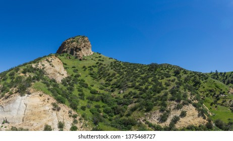 Rocky butte emerges from a grassy hillside in southern California near Santa Clarita.