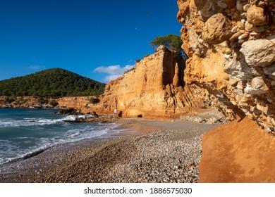 Rocky clay seashoe and the beach of Sa Caleta. Ibiza. Spain.