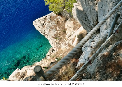 rocky cliff with security railing by the adriatic sea
