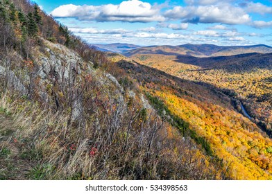 A rocky cliff side gives way to a spectacular view of the Brandon Gap in Vermont.