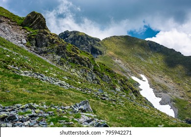 rocky cliffs on grassy slopes with snow in summer. lovely nature scenery under the cloudy sky in Fagaras mountains, Romania